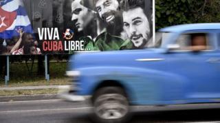 Un auto antiguo transita al lado de un aviso en la plaza de la Revolución en La Habana el 19 de marzo de 2016.