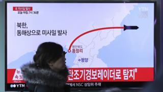 韓國首爾火車站一名女士走過正在播放朝鮮發射導彈報道的電視屏幕(6/3/2017)