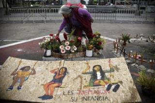 Mujer deja flores ante un cartel dedicado a las víctimas de la tragedia del Hogar Seguro Virgen de la Asunción de Guatemala.