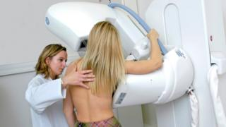 Radiographer carries out a mammogram