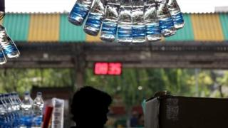 An Indian vendor sells drinking water at a railway platform