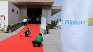 Indian workers clean the red carpet prior to the launch of Flipkart's Largest Fulfillment Centre on the outskirts of Hyderabad on October 30, 2015.