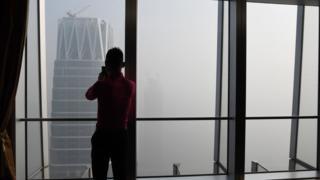 一名男子在元旦向窗外拍摄雾霾中的北京
