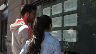 Two people look at job announcements in the window of an agency in Naples