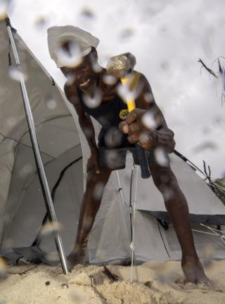 A man hammers a tent up amongst the rain