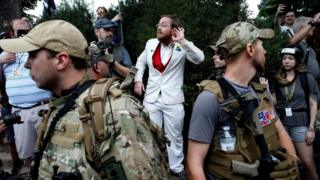 man in white suit standing behind two heavily armed men in bulletproof vests