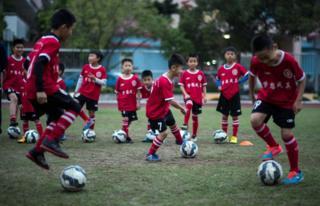 Meninos treinam em aula de futebol em Guangzhou