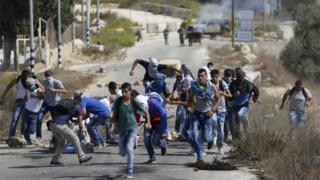 Palestinian protesters run during clashes with Israeli troops near Ramallah (05/10/15)