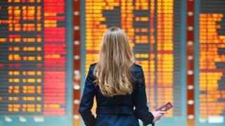 Mujer mirando panel de vuelos