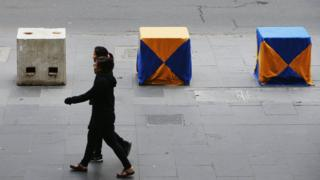 Women walk past concrete bollards in Melbourne