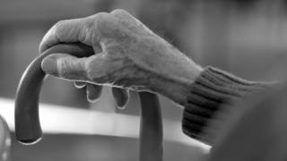 Older person holding walking stick