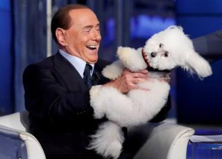 Italy's former Prime Minister Silvio Berlusconi plays with a dog