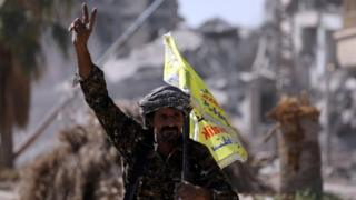A fighter from the Syrian Democratic Forces flashes a victory sign in Raqqa. Photo: 16 October 2017