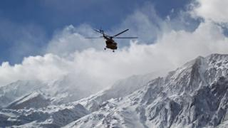 A rescue team helicopter searches for the wreckage of Aseman Airlines flight EP3704 in Iran's Zagros mountain range, 19 February
