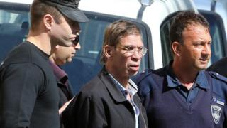 Seif Eldin Mustafa (C) flanked by Cypriot police as they leave a court in Larnaca.