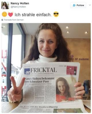 Nancy Holten holding up a newspaper with a headline saying she has her passport