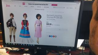 "A journalist looks at the new series of Barbie dolls, ""Inspiring Women"", featuring (L-R) Amelia Earhart, Frida Kahlo and Katherine Johnson, on 7 March 2018 in New York"