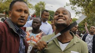 Foreigners, one holding a machete to his neck, protest during an anti-immigrant march in Pretoria, South Africa - Friday 24 February 2017
