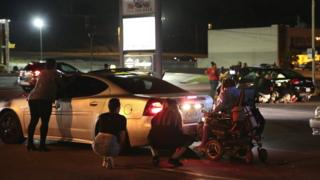 Protesters hide behind cars as shots heard in Ferguson, Missouri, on 9 August 2016
