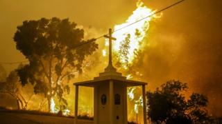 Flames rise next to a church during a fire in Pampilhosa da Serra