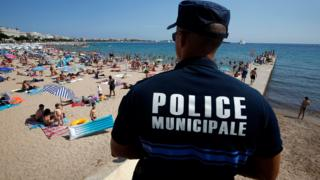 A French police officer patrols the beach in Cannes on 4 August 2016