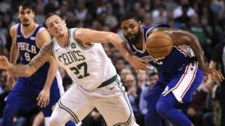 Boston Celtics forward Daniel Theis (27) and Philadelphia 76ers forward Amir Johnson (5) battle for a loose ball