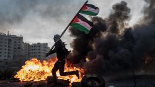 Un manifestante palestino porta una bandera palestina.