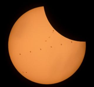 This composite image, made from seven frames, shows the International Space Station, with a crew of six onboard, as it transits the Sun at roughly five miles per second during a partial solar eclipse, Monday, Aug. 21, 2017 near Banner, Wyoming.