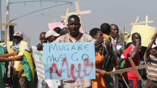 """Protesters in Harare, Zimbabwe, one holding a """"Mugabe must go"""" sign and others holding wooden crosses - Wednesday 3 August 2016"""