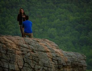 David is on one knee and Jenny is grinning whilst sitting on Hawksbill Crag