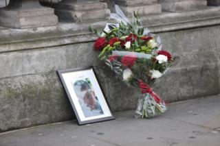 Una fotografía y un ramo de flores recuerda que el policía Keith Palmer murió en el ataque ocurrido este miércoles ante el Parlamento británico, en Londres.