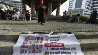 Aisha Oyebode. a founder of the Bring Back Our Girls movement speaks behind a banner with photographs of missing girls to press for the release of the remaining 112 Chibok schoolgirls at a vigil in Lagos on April 13, 2018.