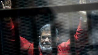 Mohammed Morsi raises his hands inside a cage in a makeshift courtroom at the police academy in Cairo, Egypt (21 June 2015)