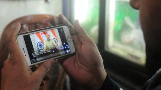 An Indian shopkeeper uses his cellphone to watch a live broadcast by Prime Minister Narendra Modi in Allahabad on December 31, 2016.