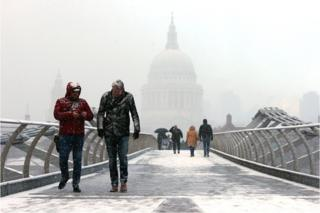 People walk over Millennium Bridge in the snow, in London