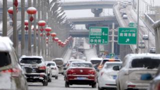 Vehicles on a snow-covered road in Urumqi, capital of China's Xinjiang region