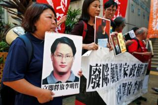 Pro-democracy protesters carry a photo of detained Taiwanese rights activist Lee Ming-Che (L) and other activists during a demonstration in Hong Kong, China 11 September 2017