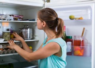 Mujer con la refrigeradora abierta