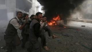 Syrian Civil Defence rescue workers carry a wounded man after what activists said was a government air strike in the rebel-held Damascus suburb of Douma (16 August 2015)
