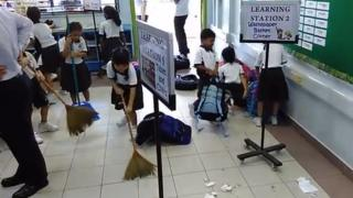 Singapore primary school pupils sweeping in a classroom