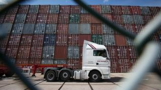 Lorry passing shipping containers