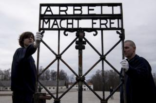 """Transport company staff carry the """"Arbeit macht frei"""" gate at the site of the former Nazi concentration camp in Dachau on 22 February, 2017."""