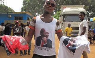 A man wearing a George Weah t-shirt attempts to sell his wares in Liberia