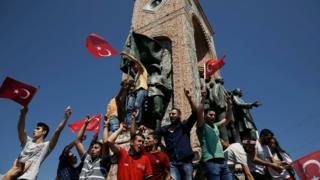 People gathered on a monument in Taksim Square