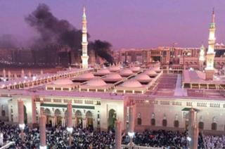 black smoke billowing from behind a huge mosque with many people outside
