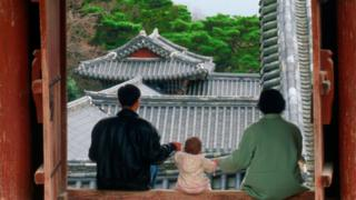 A Korean family viewed from the back at a temple