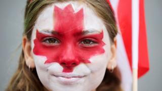 Garota com bandeira do Canadá pintada no rosto