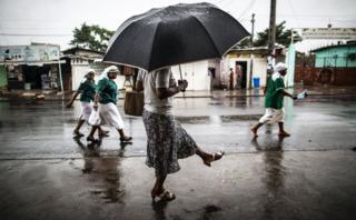 A woman washes a her foot with water streaming out of a pipe as catholic nuns leave the St. Michel Church in Libreville on 28 August 2016 after the Sunday's service