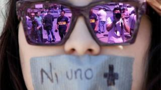 """Journalists are reflected on the sunglasses of a woman during a protest in Ciudad Juarez against the murder of the journalist Miroslava Breach. The strap reads """"Not one more"""" (25/03/2017)"""