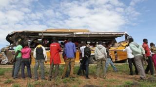 Des curieux regardent le bus impliqué dans l'accident qui a fait 26 morts
